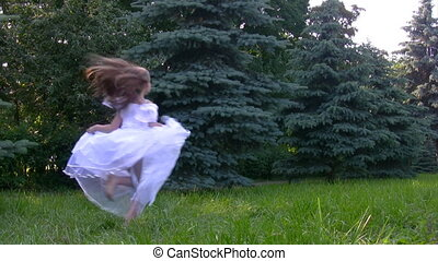 girl runs in park with conifers - girl in white dress runs...