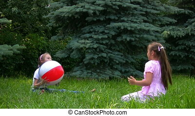 two girls sits on grass in summer park and plays
