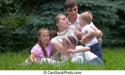 family sits on green grass in park