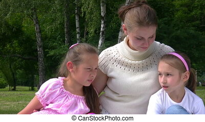 woman and two girls sits on grass in park