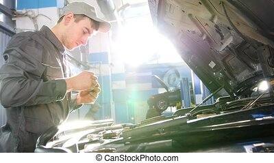 Mechanic working in the garage - repairing luxury SUV in...