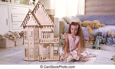 Girl playing in a toy house - Little girl playing in a toy...