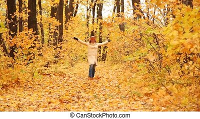 girl goes on wood road in autumn