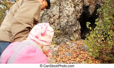 daddy with daughter come into rocky cave among trees in...