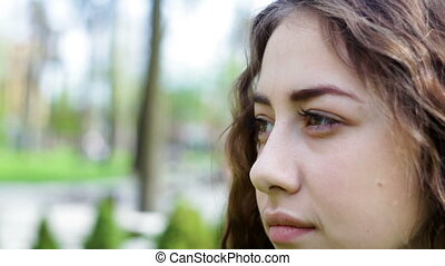 young woman looking away in a summer park. Face close-up.