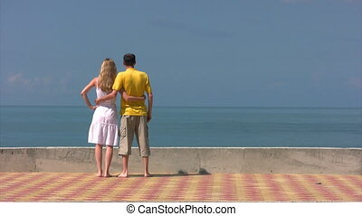 embracing man and woman stands and looks and sea
