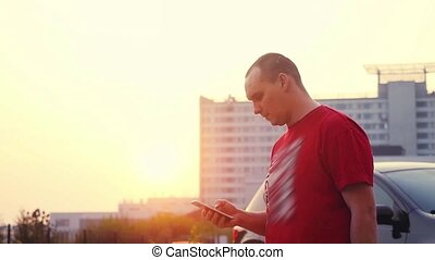 Man walking alone outdoor at sunset with smartphone in...