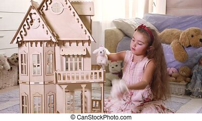 Playing with doll's house - Little girl playing with a...