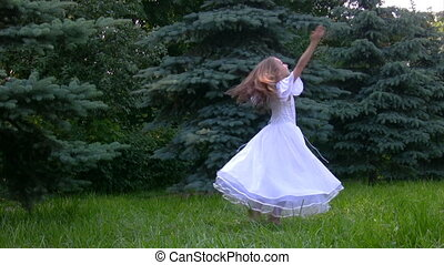 girl rotating with raised hands in park - girl in white...