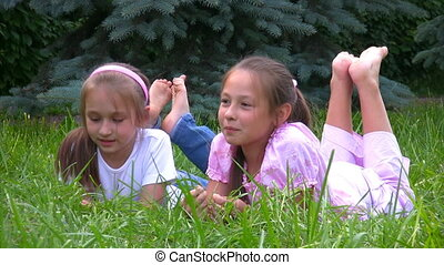 girls lying on grass in park and talks - two happy smiling...