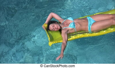 woman in bikini lies on inflatable mattress in swimming pool