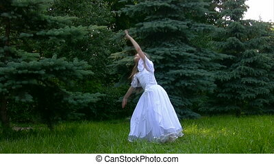 girl dressed in dances ballet in park with grass and conifers