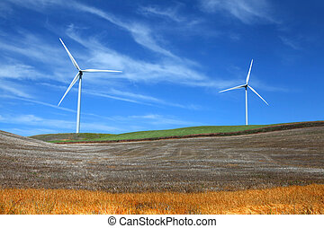 Two wind mills in the middle of wheat fields