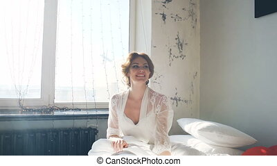 beautiful young bride smiling and having fun. Woman sits on bed in bedroom