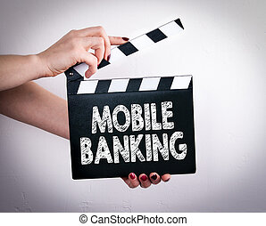 Mobile banking concept. Female hands holding movie clapper