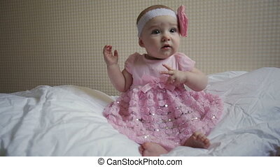 beautiful little girl in a pink dress sitting on a bed.