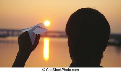 Young guy launch paper plane against the sea in slowmotion...