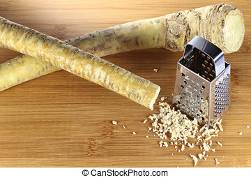 horseradish with grater on a bamboo board