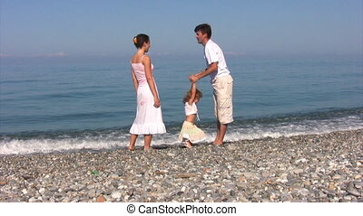 family has fun on beach against sea - family of three with...
