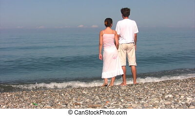 couple stands on beach and looks at sea