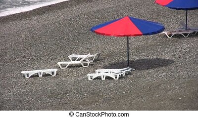 beach umbrella and beach beds on pebble coast, zoom out from...