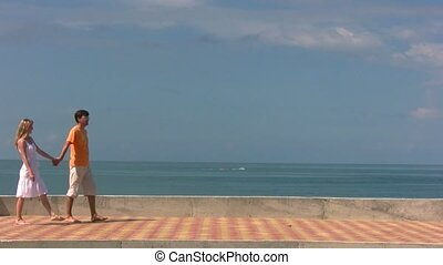 couple walks, then man holds woman looks at sea with cutter...