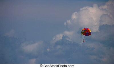 parasailing two humans on parachute flying in sky -...