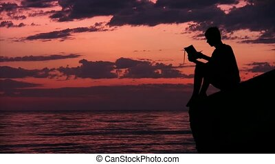 silhouette of teenager sits on rock against sky and reads book