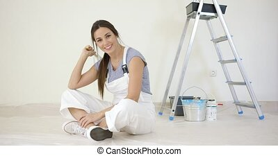 Pretty young woman renovating her home sitting on the floor...