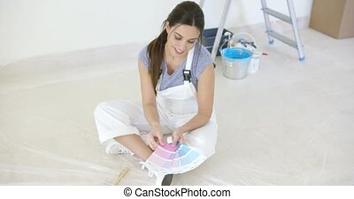 Young woman choosing her new paint for the house