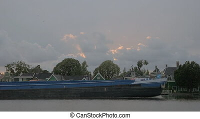 Barge sailing by the village houses - Cargo barge sailing...