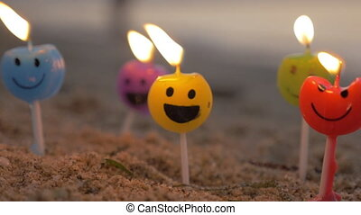 Colorful smiley candles on the beach - Slow motion close-up...