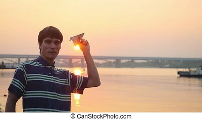Young thoughtful guy launch paper plane against the sea...
