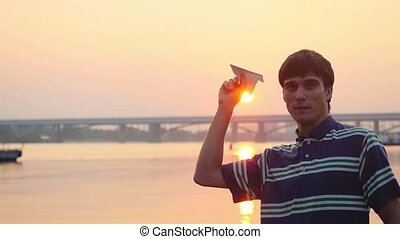 Young handsome man launch paper plane against the sea during...