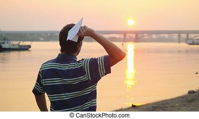 Young guy launch paper plane by the sea during sunset with...