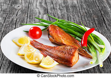 Red Sea Bass on a white dish on an old wooden table with...