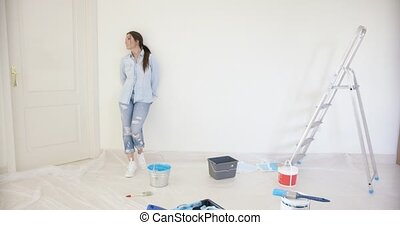 Young woman visualising redecorating her home standing...