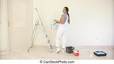 Young woman doing DIY renovations looking back over her...