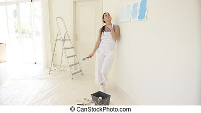 Young woman contemplating new paint for her home - Young...