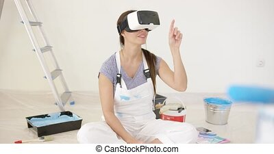 Young woman using virtual reality goggles or headset sitting...