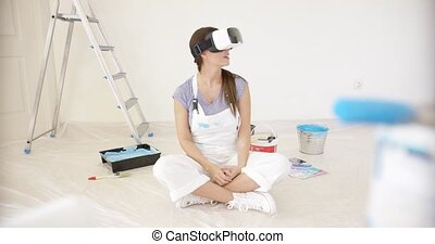 Smiling young woman wearing a VR headset sitting on the...