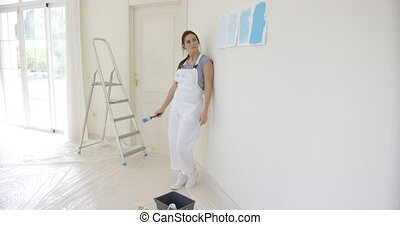 Young woman choosing a paint color for decorating and...