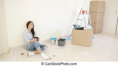 Tired young woman relaxing during renovations to her new...