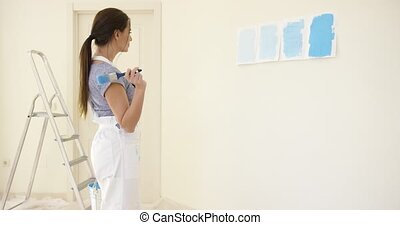 Young woman choosing a shade of blue paint from four...