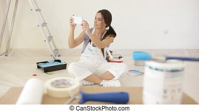 Young woman renovating her home taking a selfie of herself...