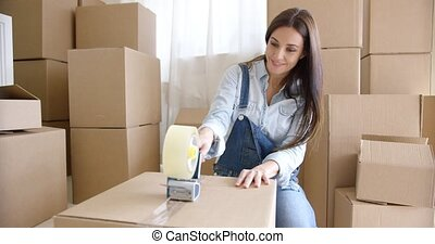 Young woman moving home packing boxes - Young woman moving...