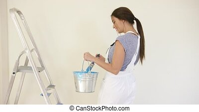 Smiling attractive woman painting her home as she...