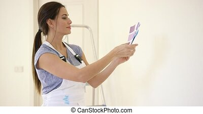Young decorator deciding on a color of paint holding up a...