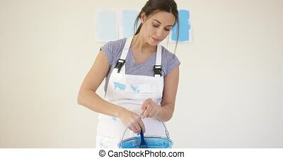 Cute playful young woman with blue paint on a brush grinning...