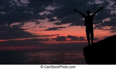 teenager stands with raised hands on rock against sunset sky